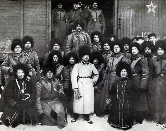 In this gathering of Russian soldiers, the officer wears the pale greatcoat.