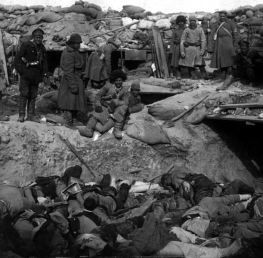 Russian soldiers view the Japanese dead.